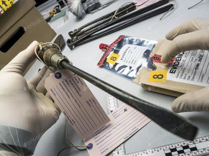 Expert police examines with magnifying glass a screwdriver in laboratory forensic equipment