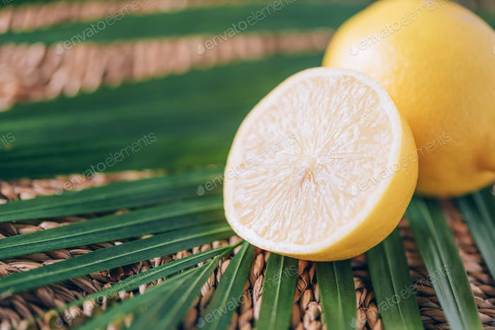 Juicy lemons with green palm leaves on rattan background. Copy space. Christmas or New year concept
