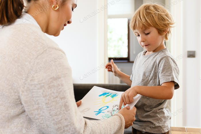 Pretty woman drawing at home with her son