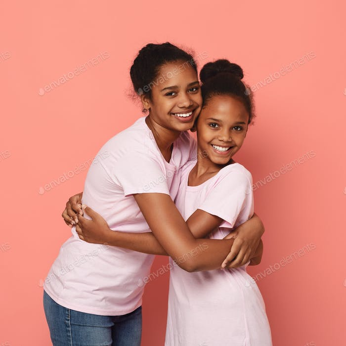 Two african girlfriends cuddling over pink background