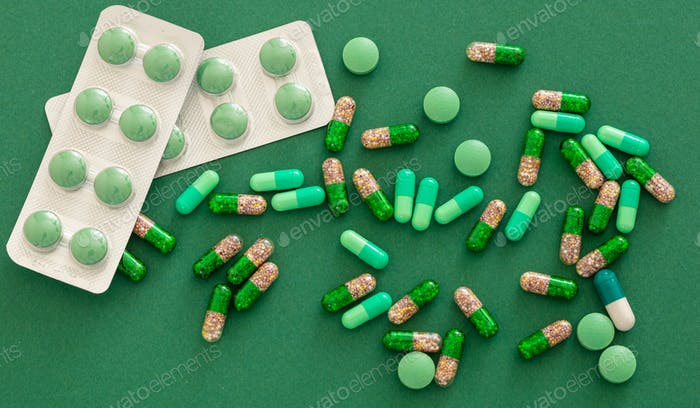 Medicine pills and capsules on green background. Health pharmacy concept