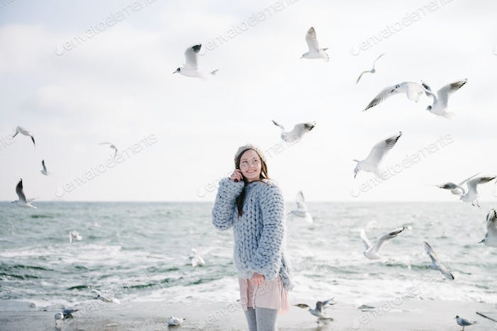 Happy Young Girl in Merino Sweater on Winter Seashore With Seagulls