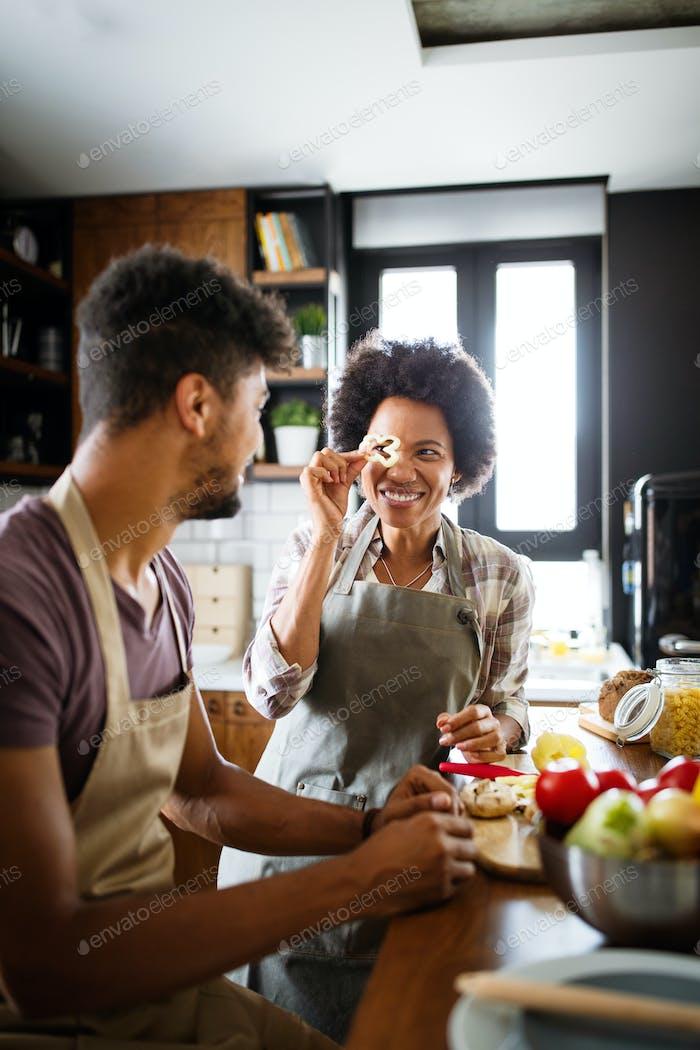 Schönes junges Paar mit Spaß und lachen beim Kochen in Küche