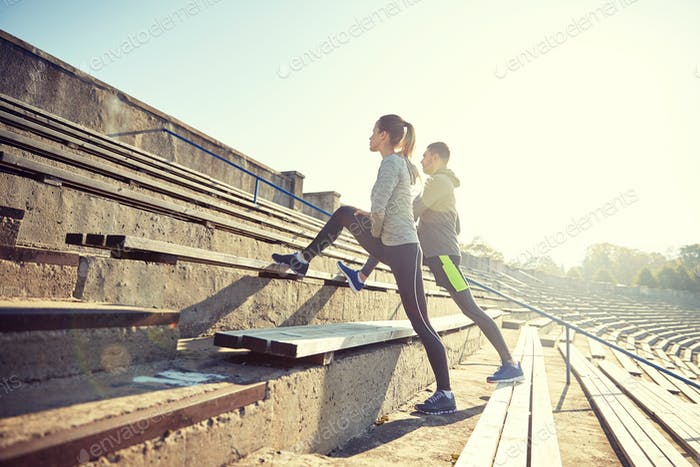 couple stretching leg on stands of stadium
