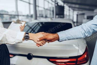 Woman car seller and man car buyer handshaking in car salon