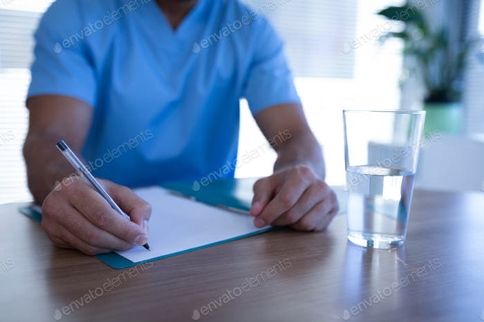 Mid section of Caucasian male surgeon writing on medical chart in clinic at hospital