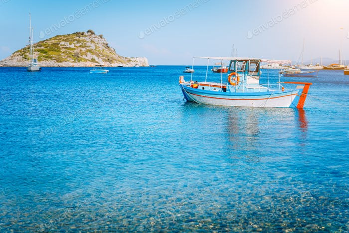 Colorful greek fishing boat at the calm clear water on early summer morning. White rock at the