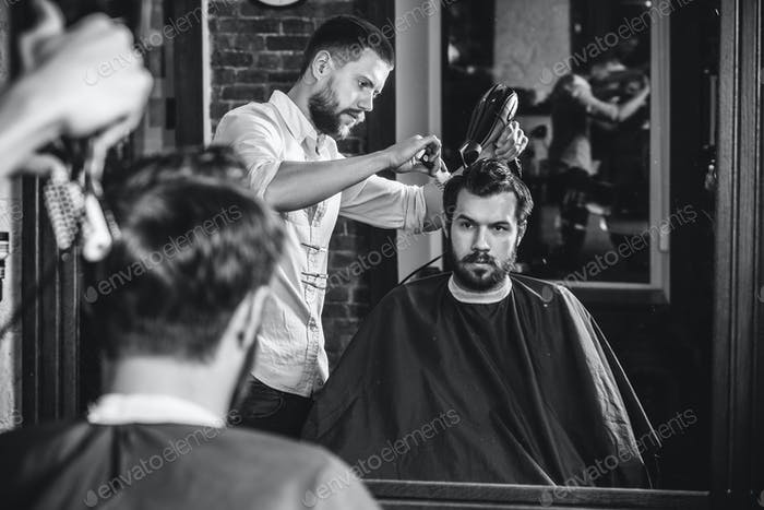 Young handsome barber making haircut for attractive man in barbershop