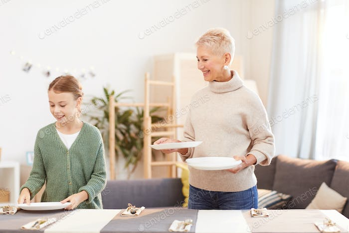 Mother and daughter serving the table
