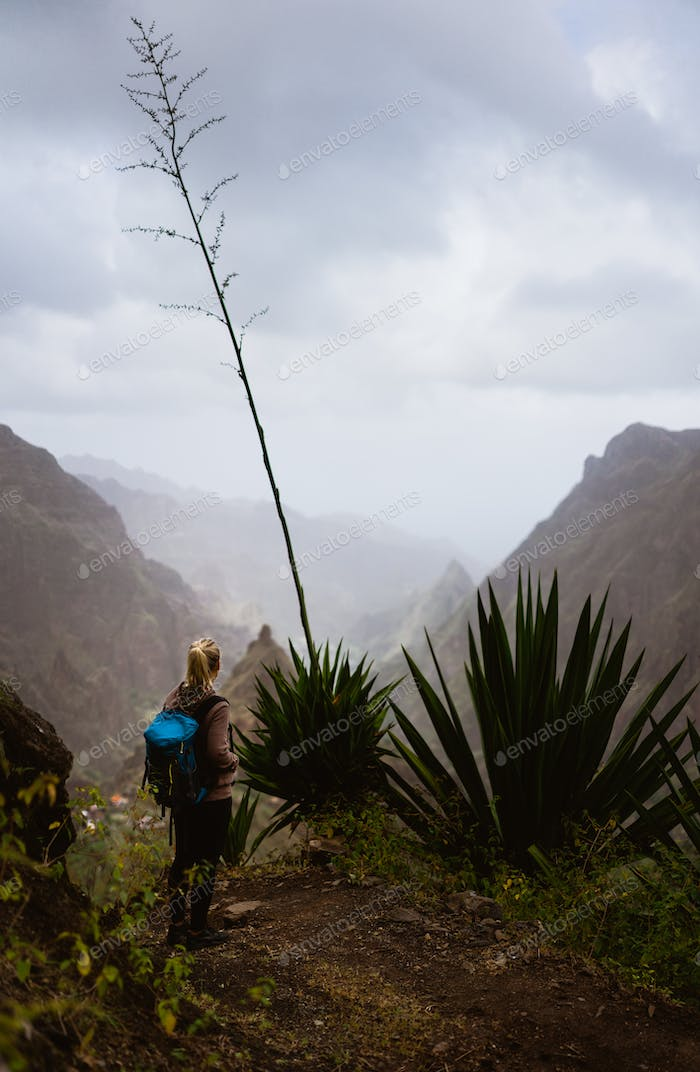Female hiker in dusty mountain terrain enjoy spectacular view of sharp summits in the fog. Santo