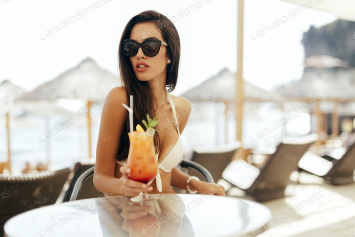 Seductive woman drinking cocktail
