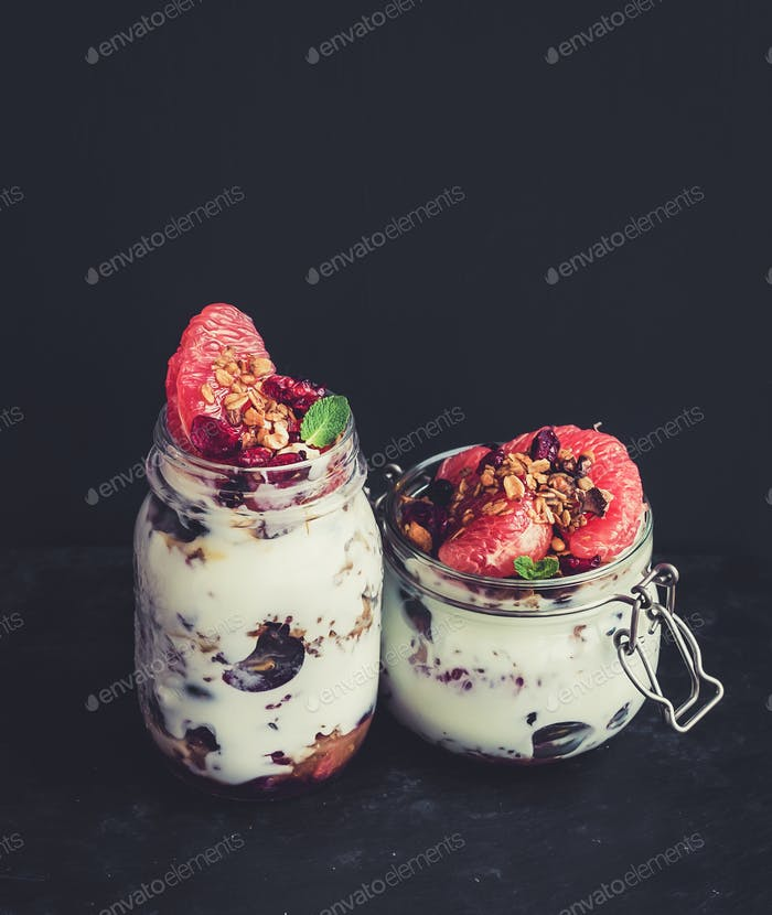 Yogurt and oat granola with grapes, pomegranate, grapefruit in tall glass jar