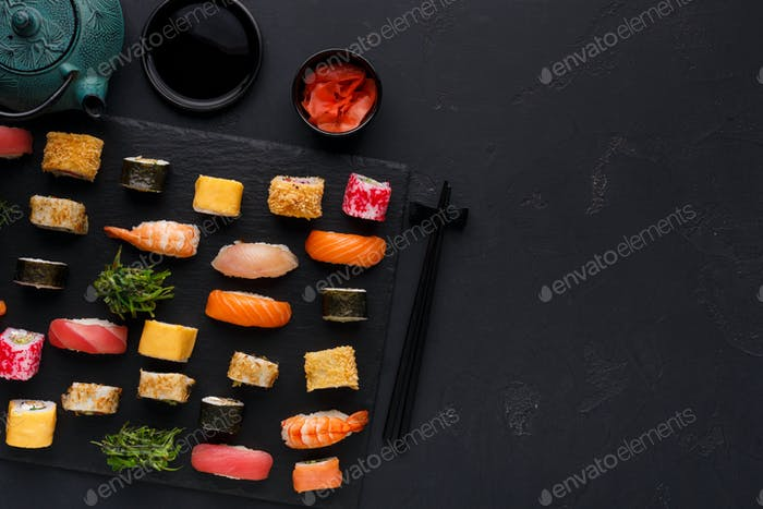 Set of sushi maki and rolls on black background