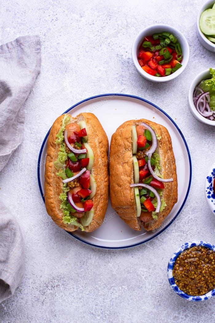Hot Dogs mit Wurst, Saucen und Gemüse