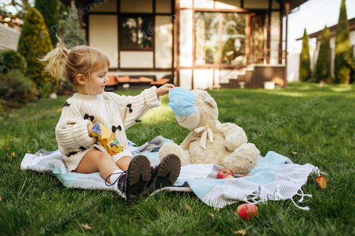 Kid play with teddy bear in the garden