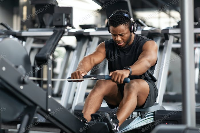 Motivated black sportsman having workout on rowing machine