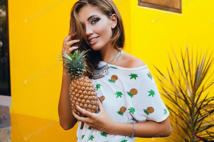 attraktive lächelnde Frau im Urlaub mit Ananas