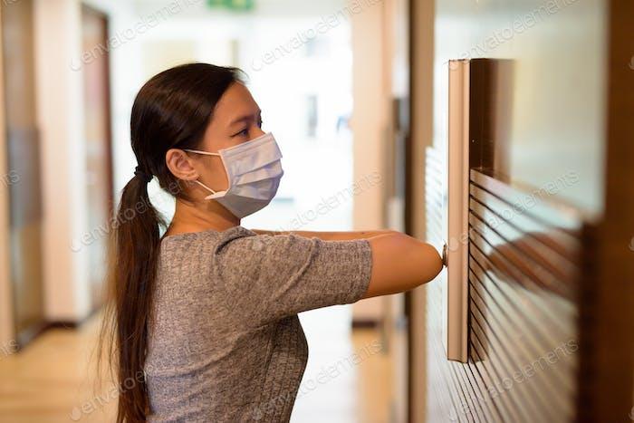 Junge asiatische Frau mit Maske drücken Aufzugknopf mit Ellenbogen zur Verhinderung der Verbreitung der