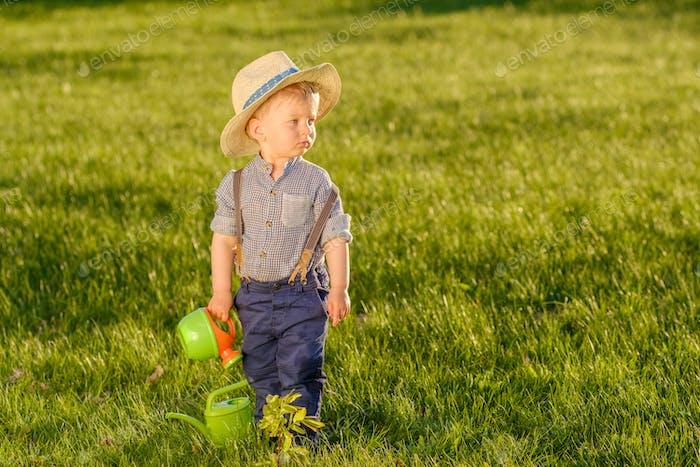 Niño pequeño al aire libre. Un Bebé de un Año con sombrero de paja Uso regadera