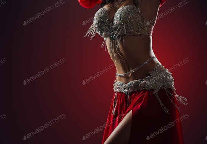 Beautiful belly dance of a girl in red decorated ethnic dress in the dark