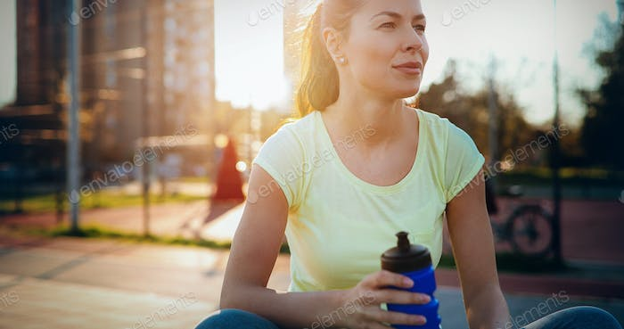 Beautiful female jogger tired after running