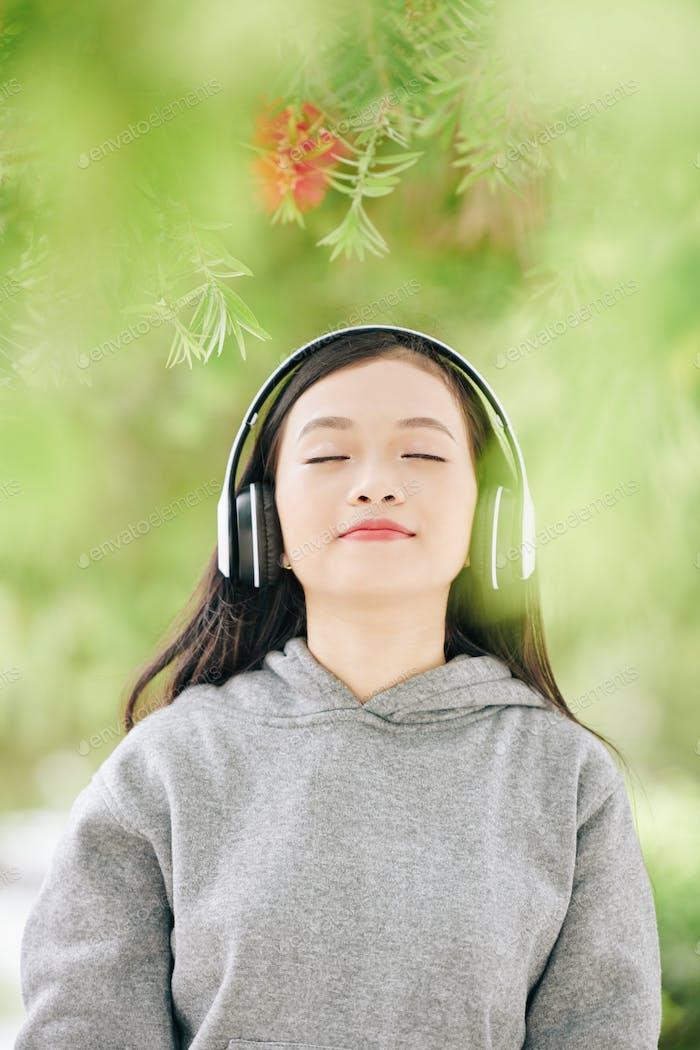 Pretty teenage Asian girl in headphones