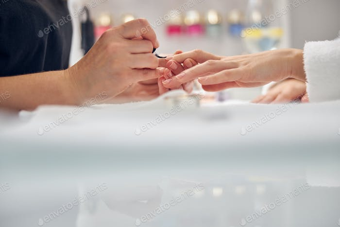 Beautician putting varnish on client finger nails