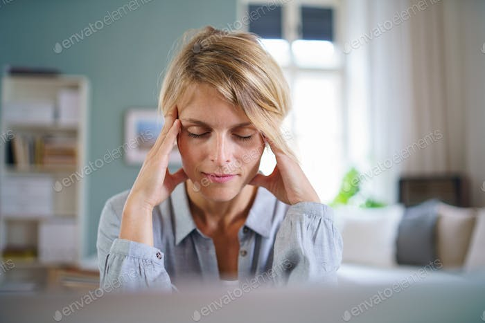 Portrait of business woman meditating indoors in office at desk, mental health concept