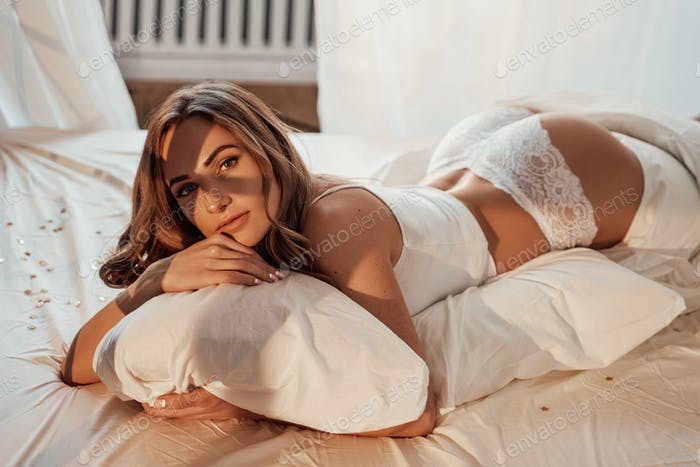 Portrait of a young and beautiful woman in white lace lingerie laying in a cozy bed