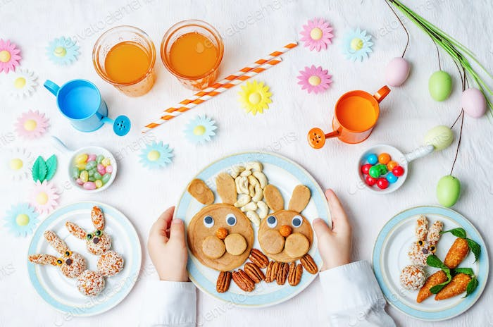 children's hands with pancakes, sweets and juice for Easter.