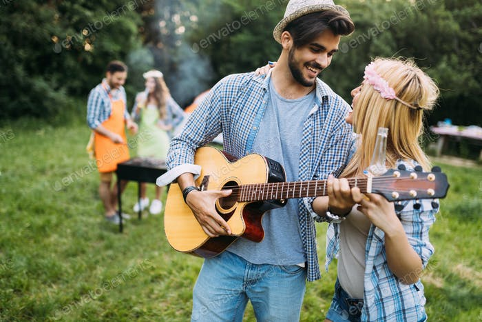 Handsome man playing guitar to his girlfriend in nature