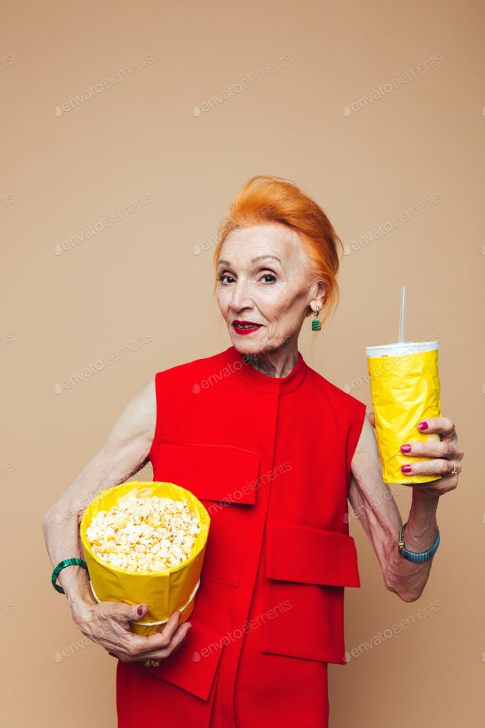 Smiling mature redhead fashion woman eating popcorn