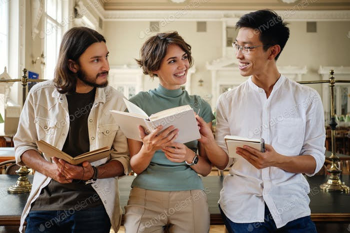 Group of young attractive multinational students happily studying together in library of university