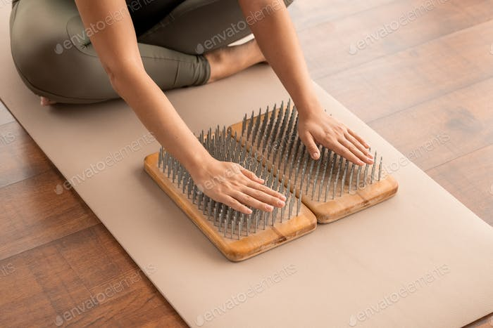 Hands of cross-legged woman in activewear sitting on mat with her palms on nails