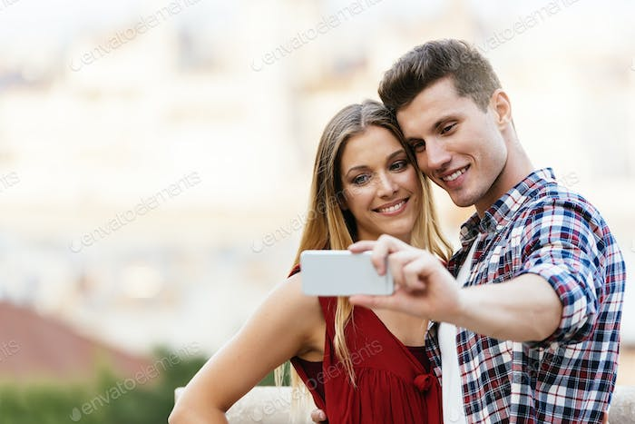 Romantic Young Couple taking a photo with mobile phone.