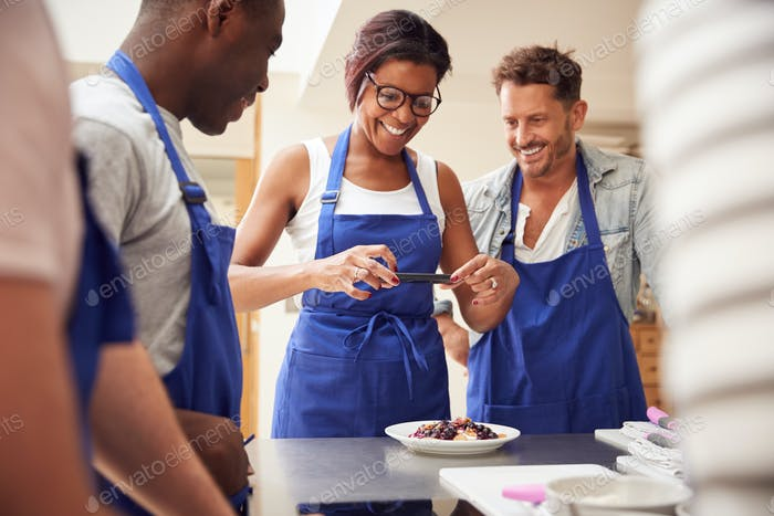 Woman Taking Photo Of Pancake Dish For Social Media In Cookery Class