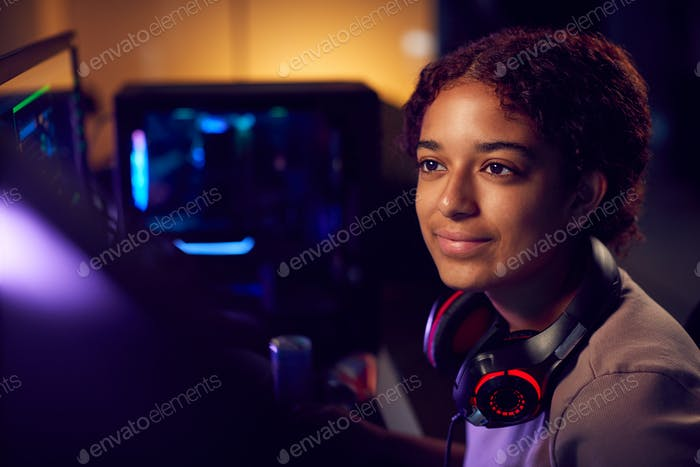 Teenage Girl With Headset Gaming At Home Using Dual Computer Screens