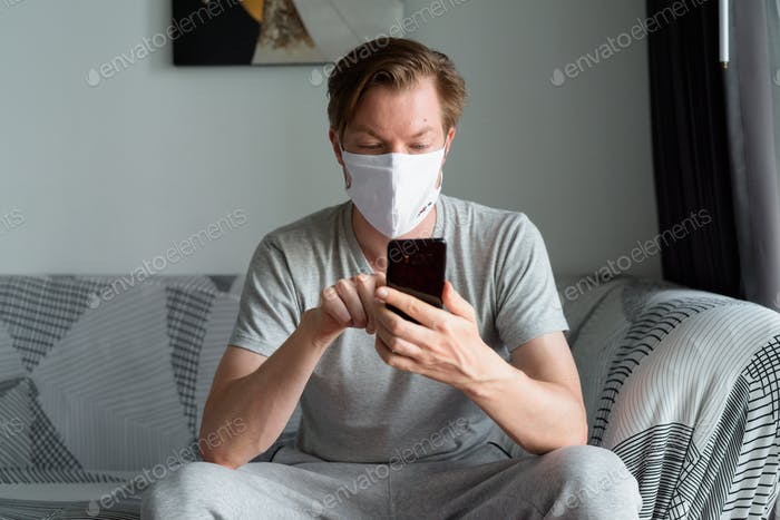 Young man with mask using phone at home under quarantine