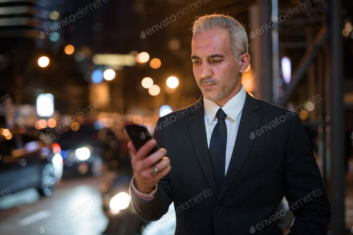 Businessman using mobile phone outdoors at night