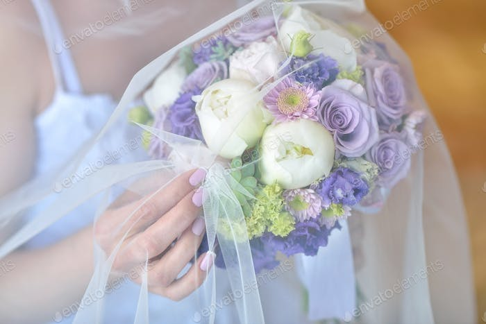 Beautiful bride is holding a wedding colorful bouquet