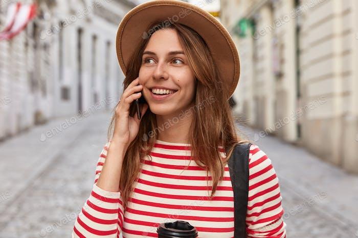 Outdoor shot of pleased Caucasian traveler talks on smart phone in roaming, enjoys cheap tariffs for
