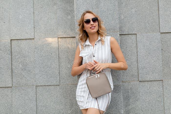 joven atractiva y elegante mujer elegante con el pelo rubio caminando en la calle de la ciudad