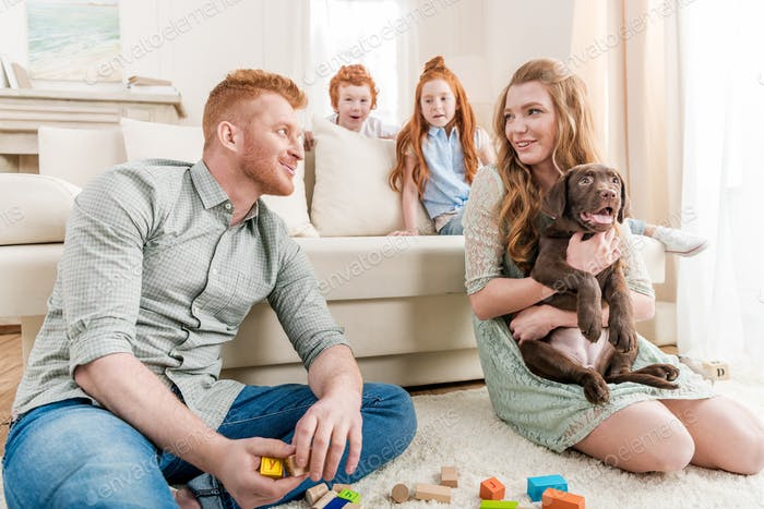 beautiful redhead family with puppy playing with constructor on floor at home, family fun at home