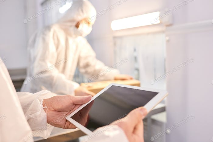 Sports nutrition factory employee using tablet