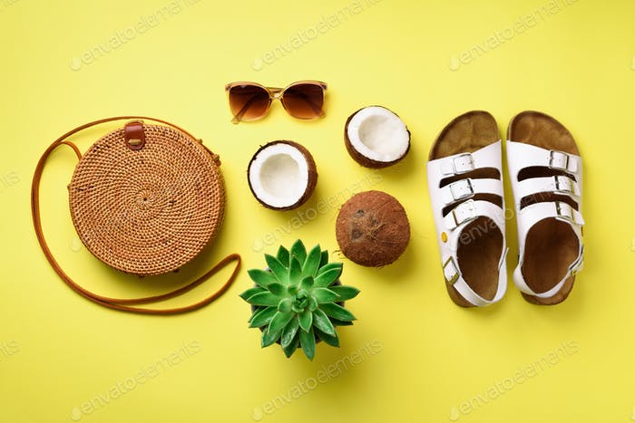 Stylish rattan bag, coconut, birkenstocks, palm branches, succulent, sunglasses on yellow background