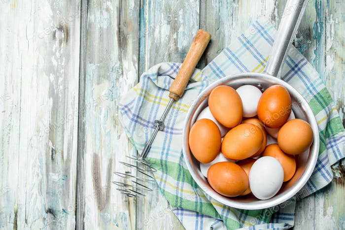Eggs in a saucepan with a whisk on napkin.