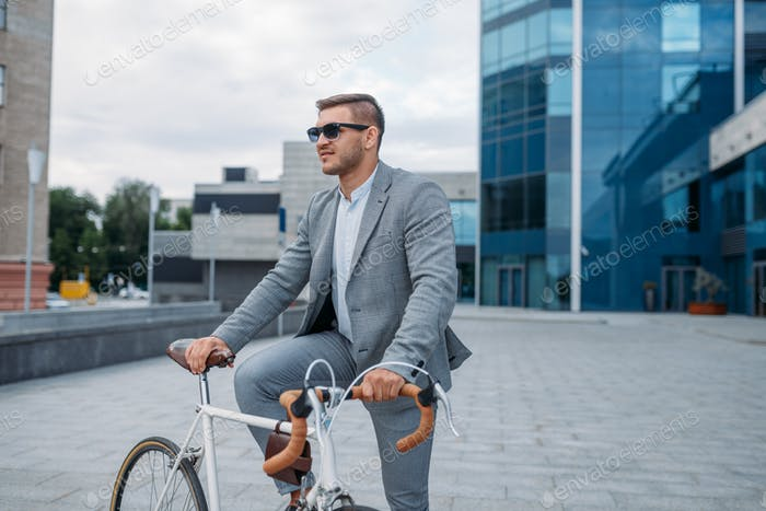 One businessman in sunglasses on bicycle, downtown