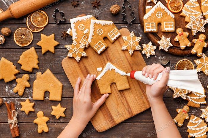 Decorating Christmas bakery. Woman glazing homemade cookies
