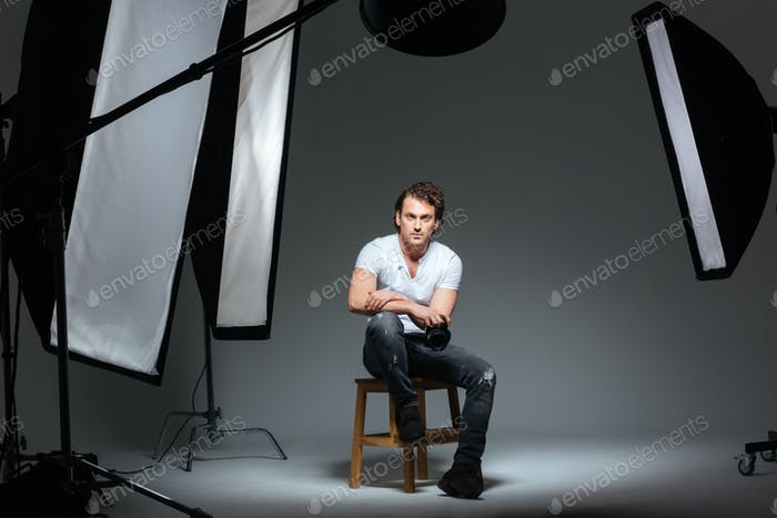 Male photograph sitting on the chair in professinal studio
