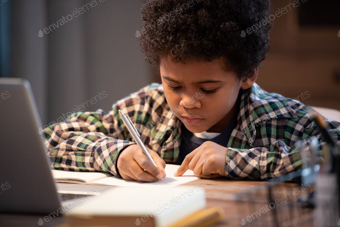 Diligent African schoolboy in casualwear making notes in copybook by table